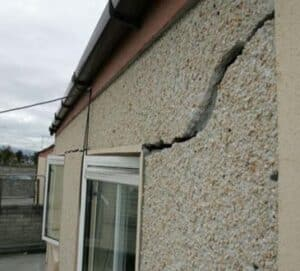 structural damage causes a crack in a wall towards a window.