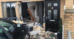 A car has crashed into a house causing major impact damage.