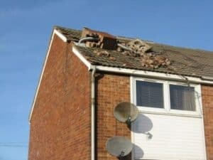 A storm causes a chimney stack to fall over and damage the roof of a house.