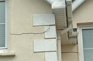A crack develops in the wall of a house after structural damage occurs.