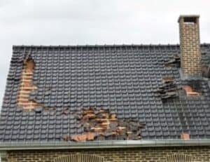A storn has damaged a house and caused roof tiles to become dislodged.